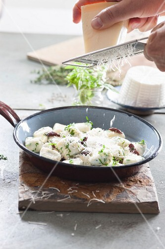 Parmesan cheese being grated over gnocchi with ricotta and herbs