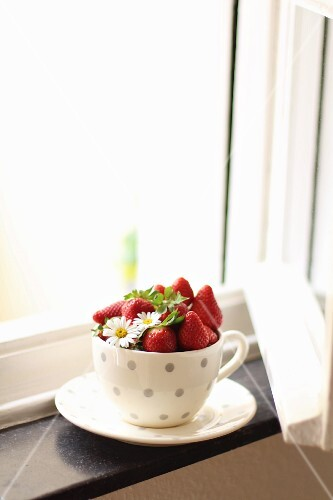 Fresh strawberries in a spotted cup on a windowsill