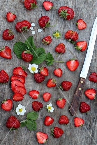 Fresh strawberries, whole and halved, on a wooden surface