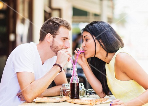 A couple sharing a cola at a pavement cafe