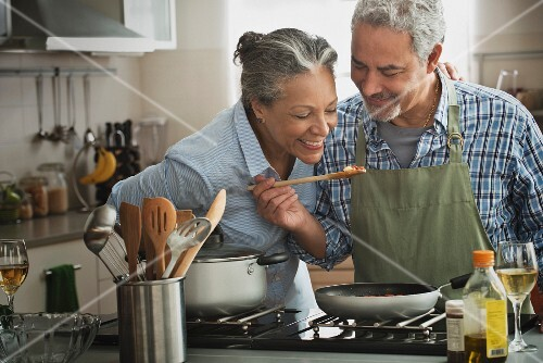 An older couple in a kitchen tasting food