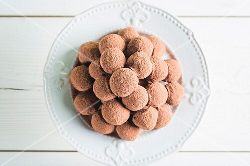 A pile of chocolate pralines on a white plate