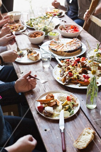 People eating together at a rustic wooden table