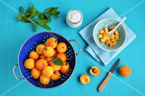 Fresh apricots in a colander and sliced in a bowl