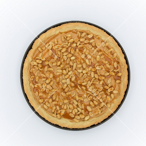A baked tarte au sucre base in a tart tin with peanut butter, peanuts and caramel sauce