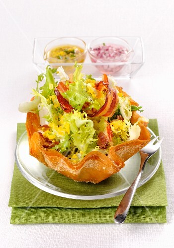 Frisee lettuce with bacon, egg and two salad dressings