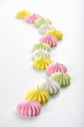 Colourful meringues on a white surface