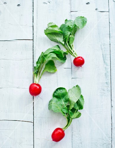 Radishes on a white wooden surface