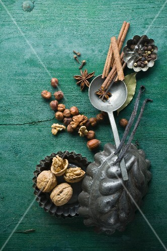 Various Christmas spices and nuts in baking tins on a rustic wooden surface