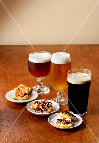 Various glasses of beer with spicy tartlets