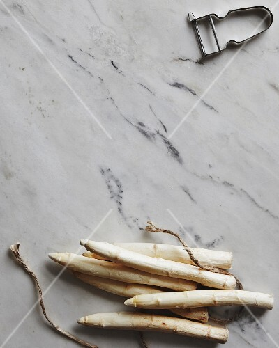 White asparagus spears, kitchen twine and a peeler