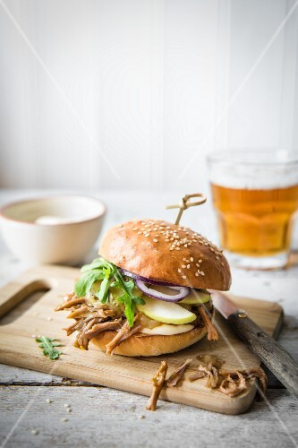 Puled pork burger with apple sauce, gherkins, onions and apple slices on a chopping board with a glass of beer in the background