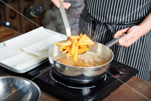 Sweet potato chips being fried in a pan