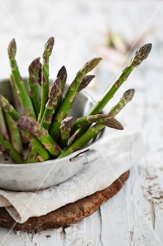 Green asparagus in a metal bowl on a linen cloth on a wooden board