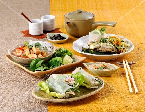 Various Thai dishes on a yellow table runner
