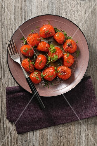 Roasted tomatoes with herbs on a plate