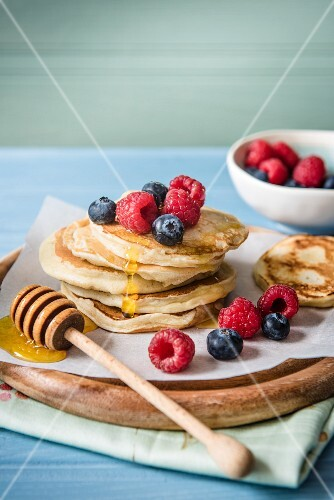 A stack of pancakes with berries and honey