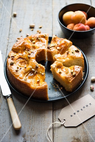 Apricot cake with pistachios and a bowl of fresh apricots