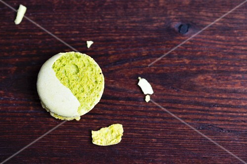 A crumbled pistachio macaroon on a wooden surface
