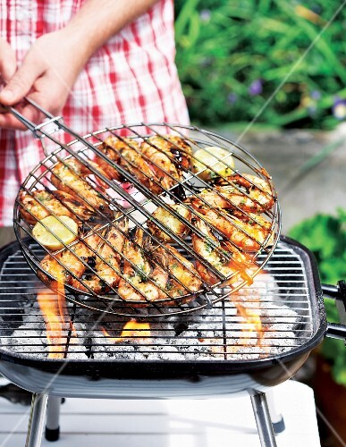 Marinated king prawns in a grilling basket being turned on a barbecue