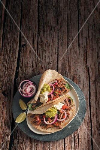 Tacos with beef brisket, salsa, red onions, sour cream and guacamole (Mexico)
