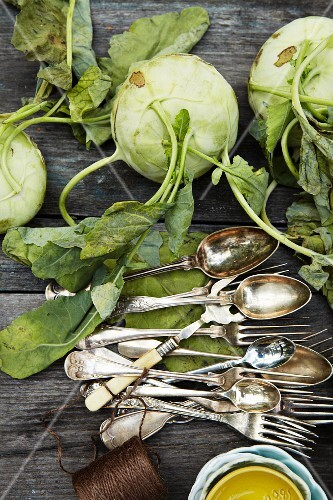 Fresh kohlrabi lying next to silver cutlery (seen from above)