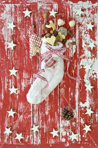 A Christmas stocking filled with nuts and biscuits on a red and white wooden surface