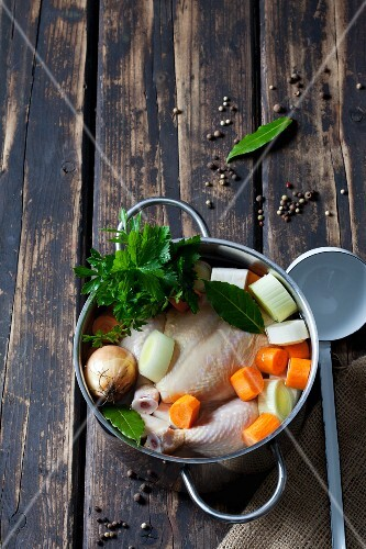 Raw corn-fed chicken with soup vegetables and herbs in a pot