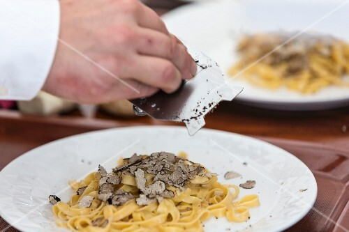 A chef grating white truffles over a pasta dish