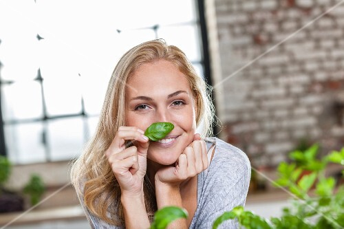 A smiling blond woman sniffing a basil leaf