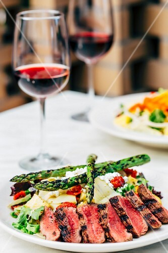 Grilled beef steak with asparagus salad and glasses of red wine on a table in a restaurant