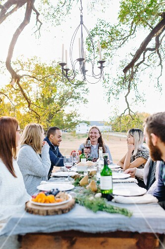 Friends eating together outside at an autumnal decorated table