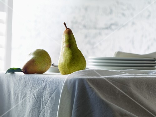 Two Abate Fetel pears on a table with a white tablecloth