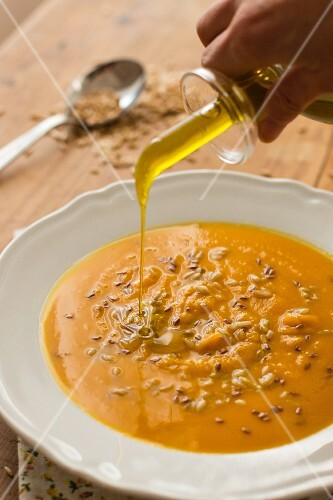 Pumpkin soup being drizzled with olive oil