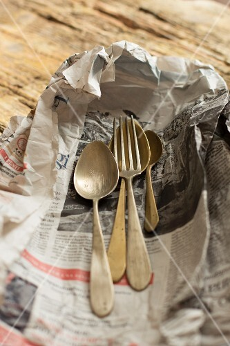 Old cutlery on a piece of newspaper