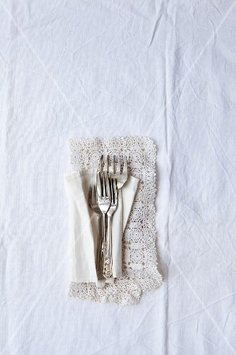 Four vintage silver cake forks on a lace doily