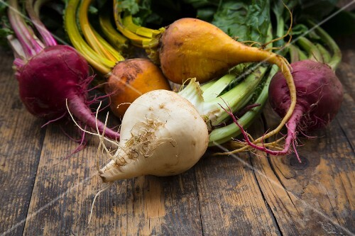 Organic beetroots, golden beets and white beets on a wooden surface