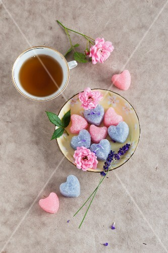A cup of tea with rose, and lavender sugar hearts