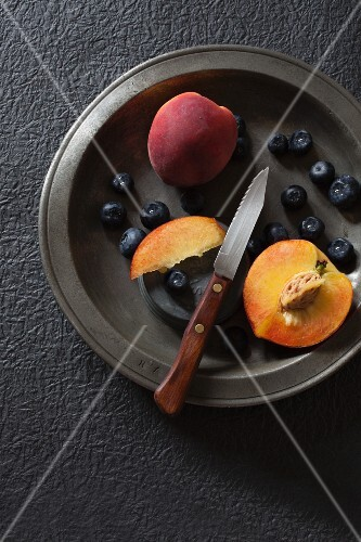 Fresh blueberries and peaches on a metal plate (seen from above)