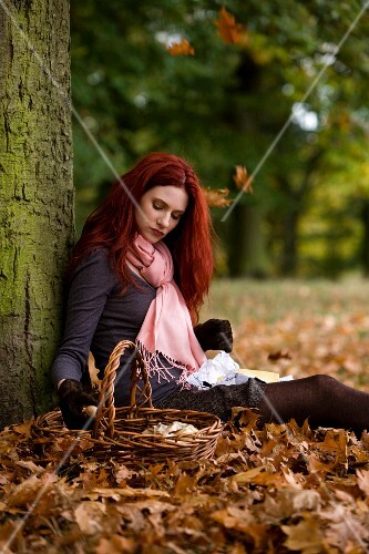 A woman with a wicker basket sitting on fallen leaves against a tree
