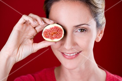 A woman holding half a fig in front of her eye