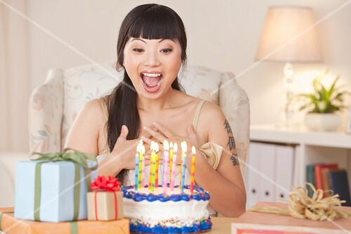 A woman getting excited about presents and a birthday cake