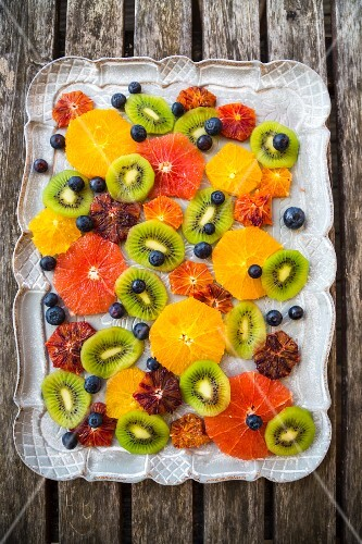 Sliced citrus fruits, kiwi slices and blueberries on a tray (seen from above)