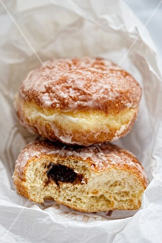 Jam doughnuts with sugar glaze in a paper bag