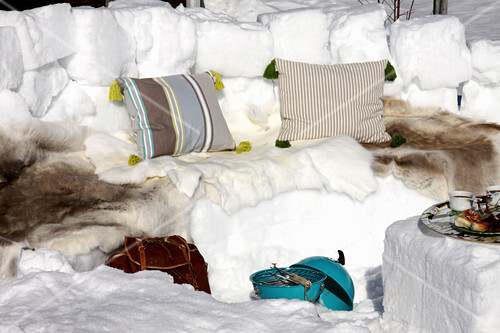Winter picnic on bench carved from snow covered in furs