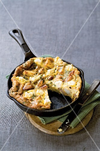 Potato frittata with feta cheese and sausage in a cast-iron pan