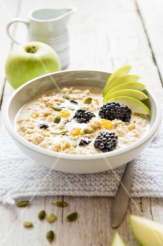 A bowl of Bircher muesli with fresh apple, blackberries, honey and seeds