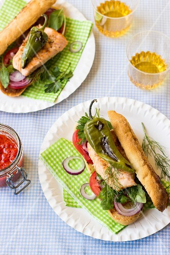 A sandwich with salmon trout, tomatoes, onions, dill, rocket, parsley and grilled peppers