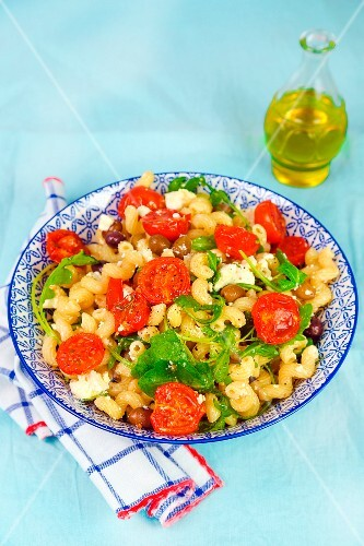 Pasta with steamed tomatoes, feta cheese, olives and rocket
