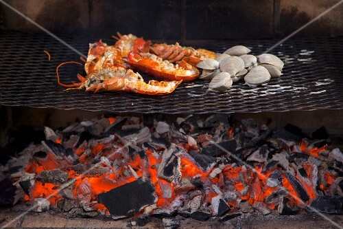 Lobster and mussels being grilled over an open fire